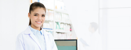 Smiling Asian female pharmacist in chemist shop or pharmacy - panoramic web banner with copy space