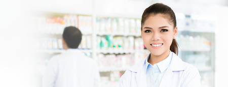 Smiling Asian female pharmacist in chemist shop or pharmacy - panoramic web banner