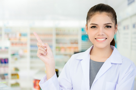 Smiling Asian female pharmacist in chemist shop or pharmacy pointing on empty space - can montage your texts or pictures above finger