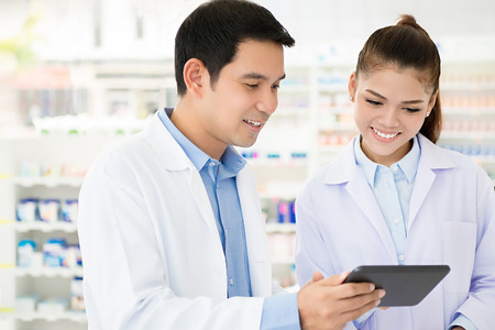 Asian pharmacist team looking at tablet computer in chemist shop or pharmacy Imagens