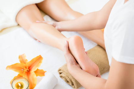 Professional therapist giving relaxing Thai oil leg massage treatment to a woman in spa