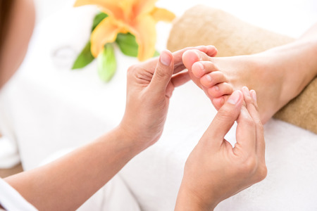 Professional therapist giving relaxing reflexology foot massage to a woman in spa
