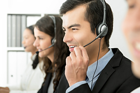 Smiling cheerful male telemarketing customer service agent with his team, call center job concept Imagens