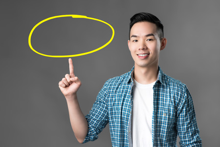 Cheerful smiling young Asian man pointing his finger up to empty circle - can put your texts inside Imagens