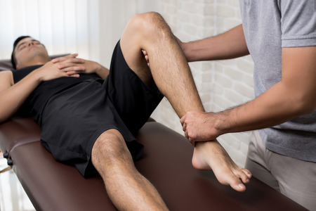 Therapist treating injured leg of athlete male patient in clinic - sport physical therapy concept Imagens