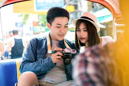 Young Asian couple tourists traveling on local tuk tuk taxi in  Khao San road, Bangkok, Thailand