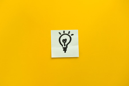 Hand drawn light bulb icon on sticky note paper representing ideas, creativity and innovation in colorful yellow background with negative space