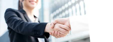 Businesswoman leader making handshake with her client outdoors in the city - panoramic banner with copy space