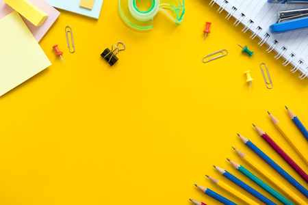 Colorful office and educational supplies on yellow background with copy space