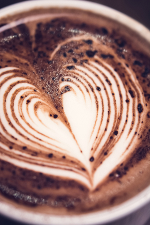 Close up of heart shape latte art on top of hot dark chocolate drink in the cup