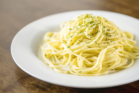 Cooked Italian spaghetti seasoning with ground parsley on white plate