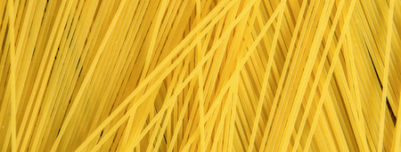 Yellow uncooked noodle raw spaghetti pasta top view, panoramic banner background
