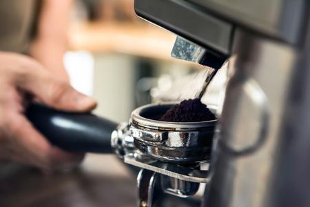 Automatische Schleifmaschine, die Kaffeebohnen in Siebträgerkorb mahlt Standard-Bild