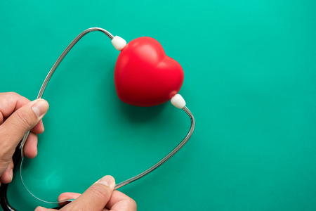 Red heart shape ball wearing stethoscope on green background, health care and medical concepts