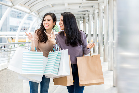 Beautiful young Asian woman friends enjoying traveling and shopping in the city during summer holiday sales season