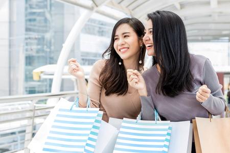 Hermosas jóvenes amigas asiáticas disfrutando de viajar y comprar en la ciudad durante la temporada de ventas de vacaciones de verano