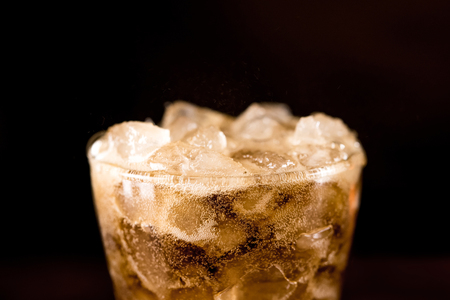 Close up of cold sparking cola sodar soft drink in the glass with foam bubble on top