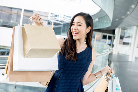 Happy beautiful young Asian woman carrying bags enjoying shopping during holiday sales season