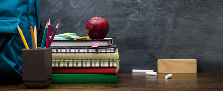 Stack of books, colorful stationery and education supplies on wooden table in classroom with blackboard in background - panoramic banner Imagens