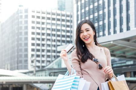 Bela e jovem mulher asiática sorrindo carregando sacolas de compras em seus braços apresentando cartão de crédito que acabou de usar para fazer o pagamento