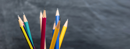 Assorted colorful sharp pencils on blurred chalkboard background, panoramic banner with copy space