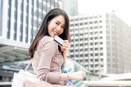 Bela e jovem mulher asiática sorrindo carregando sacolas de compras em seus braços apresentando cartão de crédito que acabou de usar para fazer o pagamento Foto de archivo