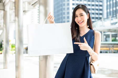 Beautiful young Asian woman showing white shopping bag