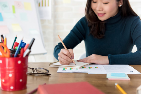 Joven estudiante universitaria asiática escribiendo en el cuaderno haciendo los deberes en la mesa