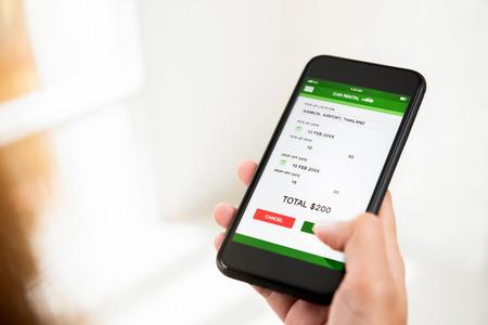 Femme confirmant le paiement en ligne pour la réservation de location de voiture sur l'application de téléphonie mobile, après avoir vérifié le prix et l'emplacement