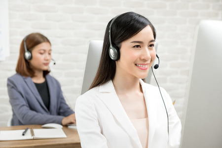 Beautiful smiling Asian businesswomen wearing headsets working in call center office as telmarketing customer service agents Banco de Imagens