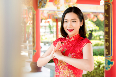 Smiling beautiful Asian woman in traditional red cheongsam qipao dress making salute in Chinese temple