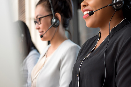 Equipo de mujeres de raza mixta que trabajan en call center como agentes de servicio al cliente de telemarketing