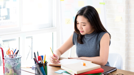 Young Asian female college student concentrating on reading book at the table preparing for examination