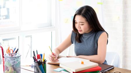 Junge asiatische Studentin konzentriert sich auf das Lesen eines Buches am Tisch, der sich auf die Prüfung vorbereitet