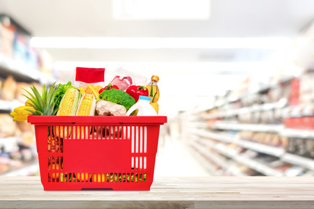 Food and groceries in red shopping basket on wood table with blurred suppermarket aisle in background