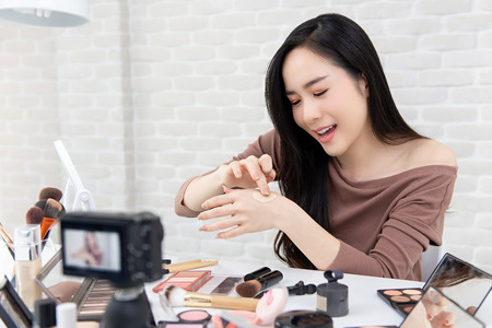 Young beautiful Asian woman professional beauty vlogger or blogger recording cosmetic makeup product review with camera