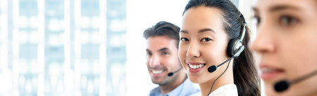 Smiling beautiful Asian woman working in call center office with international team as the customer care operators in  banner background