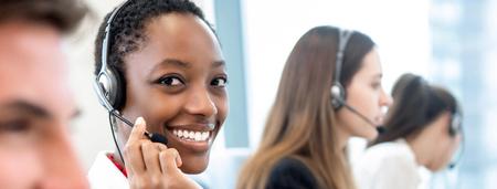Uśmiechnięta piękna Afroamerykanka pracująca z różnorodnym zespołem jako operatorzy obsługi klienta w tle transparentu biura call center