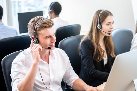 Friendly handsome man working in call center headquarters office with team as telemarketing customer service agents
