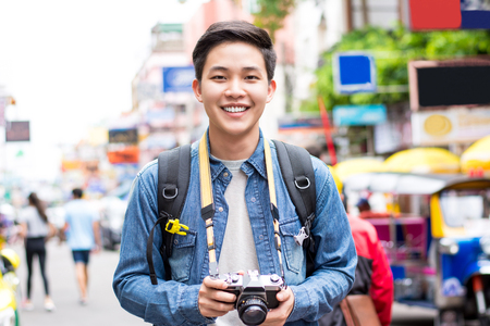 Asian male tourist photographer backpacking in Khao san road,  Bangkok, Thailand on holidays
