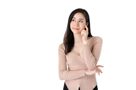 Young beautiful pensive Asian woman looking aside with hand on cheek wondering or thinking about  something, studio shot isolated on white background
