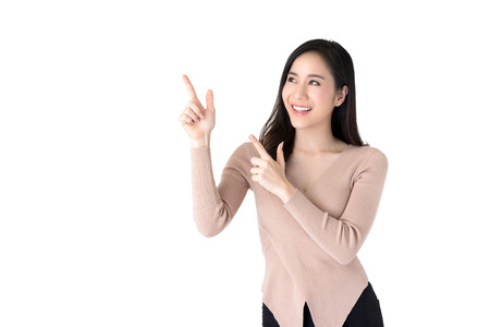 Beautiful young casual Asian woman smiling and pointing hands to empty space aside, studio shot isolated on white background 版權商用圖片