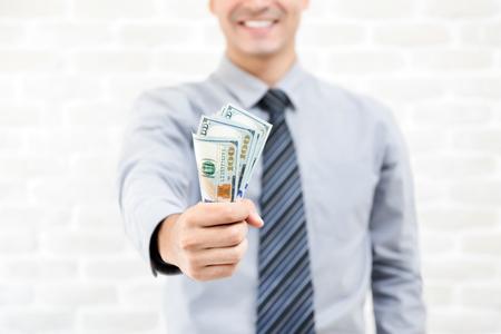 Uomo d'affari che afferra soldi, dollari degli Stati Uniti, in mano