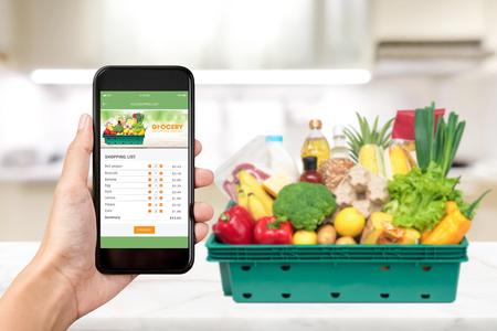 Aplicación de compras en línea de comestibles en la pantalla del teléfono inteligente con comida en casa en segundo plano.