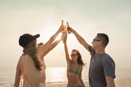 Group of friends claging beer bottles having celebration party and drinking at the beach in summer Banco de Imagens