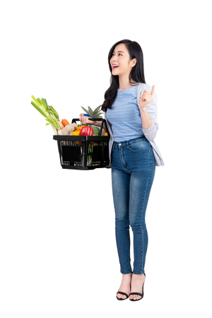 Beautiful Asian woman holding shopping basket full of vegetables and groceries, studio shot isolated on white background Фото со стока