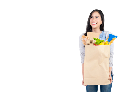 Beautiful Asian woman holding paper shopping bag full of vegetables and groceries looking at the space aside, studio shot isolated on white background Фото со стока