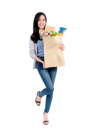 Beautiful smiling Asian woman holding paper shopping bag full of vegetables and groceries, studio shot isolated on white background