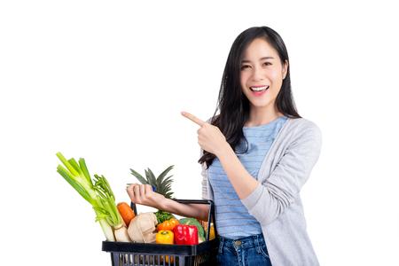 Piękna Azjatycka kobieta trzyma koszyk pełen warzyw i artykułów spożywczych, studio strzał na białym tle