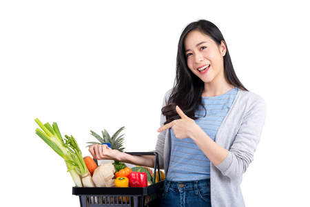 Beautiful Asian woman holding shopping basket full of vegetables and groceries, studio shot isolated on white background Stok Fotoğraf